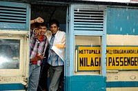 Loughing young indian men on board the Nilgiri Mountain Railway at Coonoor railway station in rain. India, Tamil Nadu, Coonoor 2005. - Info: The Nilgi...
