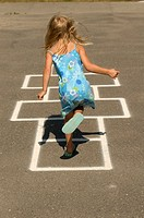 Young girl, 4 years old, playing hopscotch in park.  White Rock, BC, Canada.  Near Vancouver