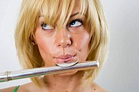 Young (20´s) blond caucasian woman accesses her right brain while playing the flute in studio portrait