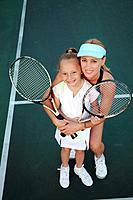 Mother and daughter posing with tennis rackets