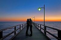Young couple on sea bridge kissed at sunrise, Island Usedom, Baltic sea, Mecklenburg Vorpommern, Germany