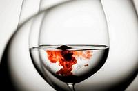 Gota roja en copas de agua. Bodegón.