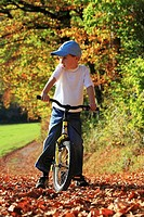 boy on his bicycle, standing still and looking in to the distance, on road with leaves in fall, autumn foliage covering path in forest, autumn, fall, ...