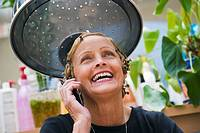 Older woman with hairclips using mobile phone, smiling, portrait