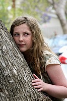 13-year-old girl with blonde-brown long hair and freckles, half leaning against, half hiding behind a tree, up-to-something expression
