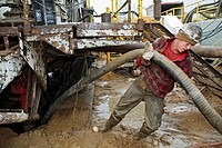 Mancelona, Michigan - A worker struggles with a hose while dismantling a natural gas drilling rig in the Antrim Shale field of northern Michigan