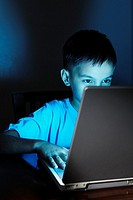 Young Asian boy using laptop at night.