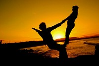 Performers practice their dance routines at the beach during sunset in Byron Bay. New South Wales, Australia