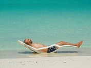 Young man, bald with a beard, lying in a hammock in the sun on the edge of the Caribbean beach in Cayo Levisa Cuba.