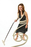 Young woman homemaker tangled in vacuum cleaner hose on white background