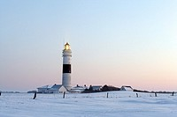 Lighthouse Kampen on snow covered fields with a bright blue sky during sun set, in operation with the light beam visible, Sylt, Northfrisian Islands, ...