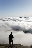 A hiker takes in the view of undercast from the summit of Mount Osceola in the White Mountains, New Hampshire USA