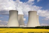 landscape showing 4 cooling towers of Temelin nuclear power plant station and yellow rape field, Czech Republic, Europe.