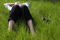 middle aged man wearing suit trousers shirt and tie lying in long grass relaxing with shoes and socks off