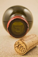 Close-up of a Wine Bottle Cork and Wine Bottle on a Beige Textured Paper Background, Studio Composition