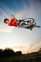 Teenage boy on trials bike at a skateboard park performing aerobatic stunts, Aberystwyth Wales UK