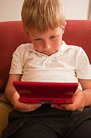 A  close up picture of a six year old boy playing on a nintendo DS handheld computer game console in the Uk