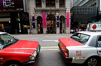 Taxis await passengers in downtown Hong Kong.