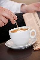 Man stirring a cup of coffee