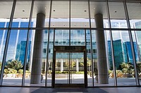 Attractive courtyard patio area as seen through the glass front door entrance to a modern office building complex in Silicon Valley. San Mateo, Califo...