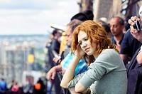 Sad girl among tourists on Eiffel Tower  Loneliness, misunderstanding
