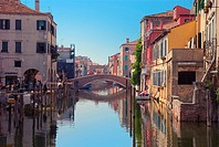 Bridge over canal in Chioggia, Italy  Typical Italian houses and gondolas