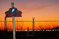 Wooden post indicating the aterdecer Motorcycle Parking on a red sky near the airport of Ibiza