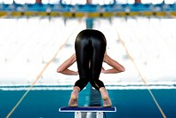 Young woman about to dive in swimming competition