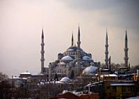 Shy sunrise in winter on the snowy Sultan Ahmed Mosque Turkish: Sultanahmet Camii also called blue mosque, Istanbul, Turkey, with the fogy Bosphorus i...