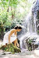 Young attractive brunette woman, wearing a white dress, touching the water in a beautiful natural place, with a waterfall and assorted vegetation