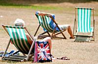 Visitors relax in the summer on deck chairs, St James park, London, UK