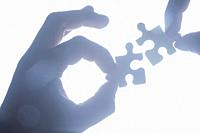Hand holding jigsaw piece silhouetted and ijn blue tones