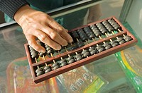 Abacus counting machine calculator  Woman hand using abacus adding subtracting sum on shop counter in Chinese shop, China