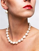 close up view of models neck with string of pearls with earrings