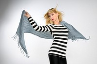 Young blond woman in striped top holding a scarf in the wind on gray background