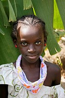 Portrait of an African girl with white spots on her face looking at the lens with banana leafs as background, Tanji Village, Tanji, Gambia, Africa