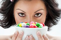 Beautiful candy girl closeup holding a bowl of colorful bubblegum candy balls in front of her face