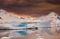 Storm clouds gather at sunset over peaks around Wiencke Island, Neumeyer Channel, Antarctic Peninsula.
