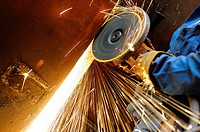 Close-up of heavy industry worker with grinding machine throwing a splash of sparks