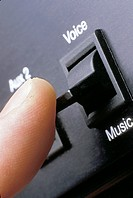 close up of finger about to flick the switch in the recording studio from the vocal track to the music