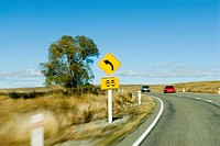 Motion blur effect - left bend, 85 kph speed advisory sign  Red and silver cars approaching