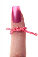 Woman´s finger with pink string around it, for a reminder