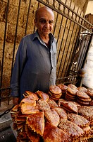 egyptian man selling pastries and egyptian savoury snacks outside mosque, islamic cairo, cairo, egypt