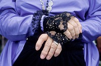 Close up of a middle aged woman´s hands folded in repose, her costume that of the middle eighteen hundreds featuring black lace cuffs