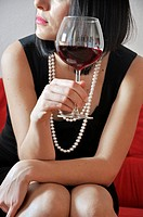 Young woman holding glass of red vine