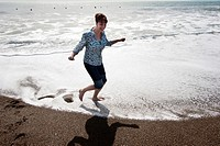 A woman splashes about in the Pacfic Ocean at Rodeo Cove near San Francsico, CA