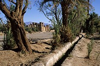 Near Skoura, Morocco - Irrigation Channel Parallel to Dry River Bed, Kasbah Ameridhil in Background  This area has had greatly reduced rain during the...