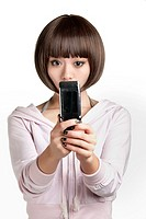 Beautiful Chinese woman using a cell phone on a white background