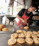 muslim tea shop owner preparing hot crispy roti, muslim community , mae sot, northern thailand