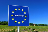 Country sign of the Grand Duchy of Luxembourg on the basis of the European flag with the circle of twelve golden stars at the national border near Sch...